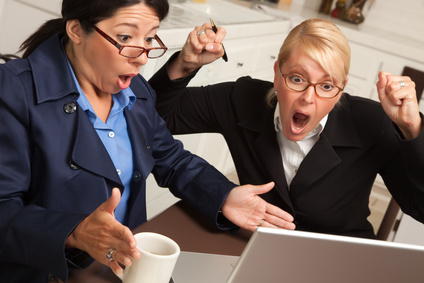 Businesswomen Celebrate Success on the Laptop in the Kitchen.