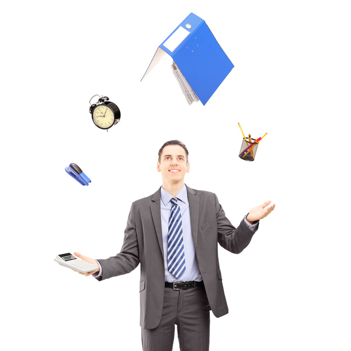 Young businessman in a suit juggling with office supplies, isolated on white background